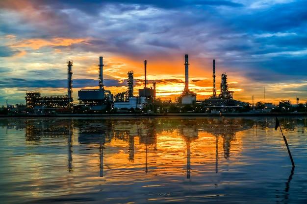 Foco suave da refinaria de petróleo no crepúsculo e reflexão da água, rio chao phraya, tailândia