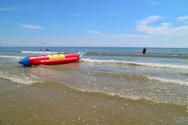 Foco suave de bela vista das ondas na praia com banana boat e céu azul