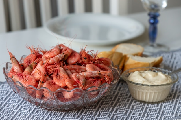 Foco suave de camarões cozidos em uma tigela de vidro com molho de alho e pão na mesa da cozinha