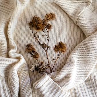 Foco suave de cardos secos em tecido de malha branco