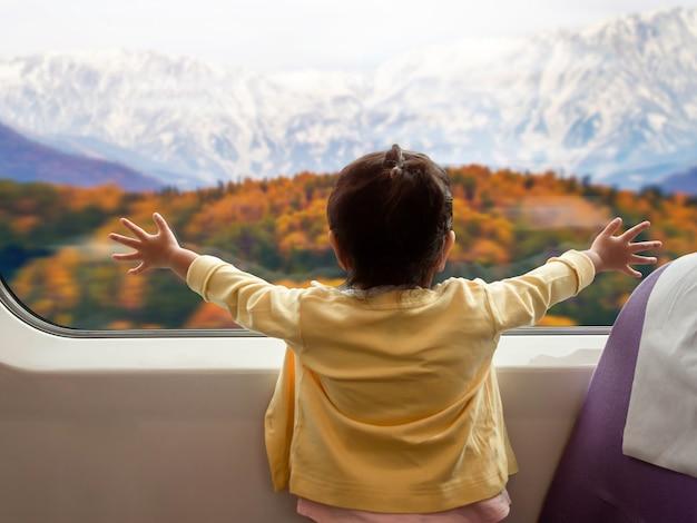 Foco suave de crianças felizes e animadas viajando de trem com a família durante o outono