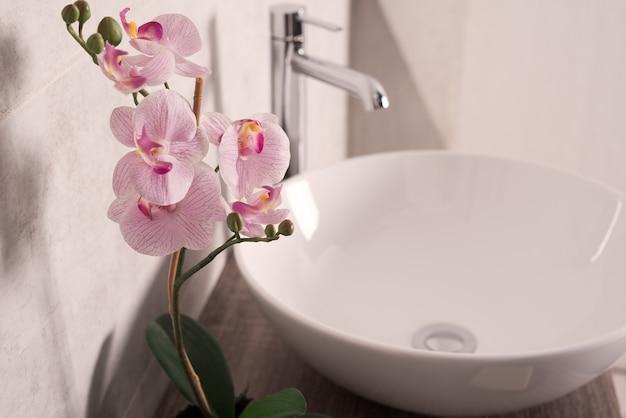 Foco suave de flores de orquídeas ao lado de uma pia em um banheiro