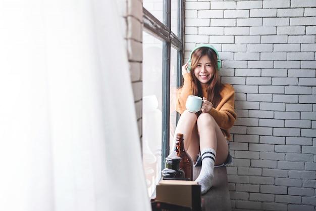 Foco suave de mulher jovem relaxante com música de fone de ouvido na janela perto de casa aconchegante