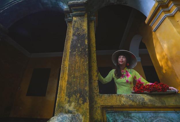 Foco suave de mulher vietnamita em vestido tradicional em pé na frente do velho residente
