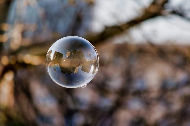 Foco suave de uma bolha com reflexo de edifícios e árvores da cidade