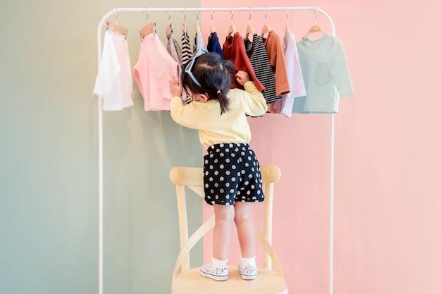 Foco suave de uma criança de dois anos escolhendo seus próprios vestidos de crianças