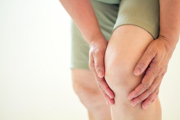 Foco suave de velhas mulheres asiáticas a lesão no joelho em fundo branco