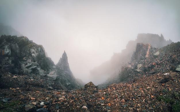 Foco suave. desfiladeiro perigoso. névoa dramática entre montanhas rochosas gigantes. vista atmosférica fantasmagórica para um grande penhasco no céu nublado. nuvens baixas e belas montanhas rochosas. lugar misterioso de cenário minimalista.