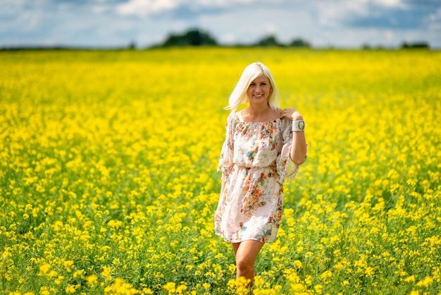 Foco suave e seletivo. mulher bonita, atraente e loira em um prado de flores amarelas.