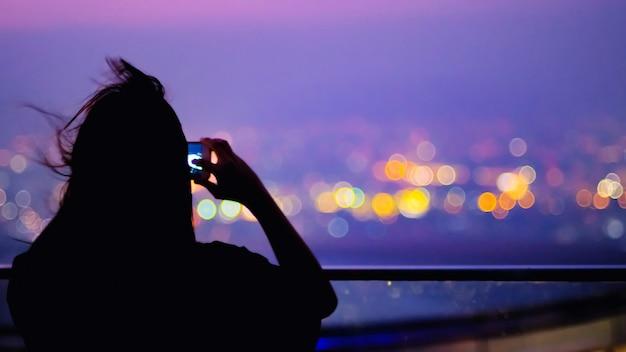 Foco suave e silhueta de mulher jovem com cabelos longos para tirar uma paisagem urbana de foto no topo do prédio com bokeh colorido cidade luz abstrato e copiar espaço para texto.