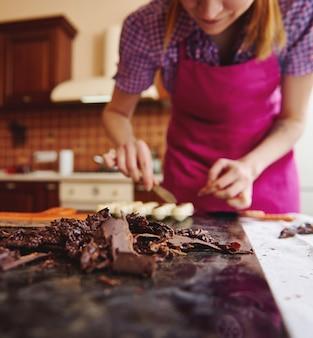 Foco suave em massa de chocolate temperado deitada sobre uma mesa de mármore na superfície de um confeiteiro borrado trabalhando na preparação de trufas de chocolate caseiras