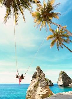 Foco suave em mulher em balanço de bali na praia de diamond beach, ilha de nusa penida em bali, indonésia