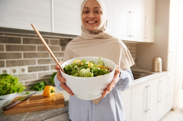 Foco suave em uma saladeira branca com vegetais fatiados nas mãos de uma linda mulher muçulmana sorridente em hijab