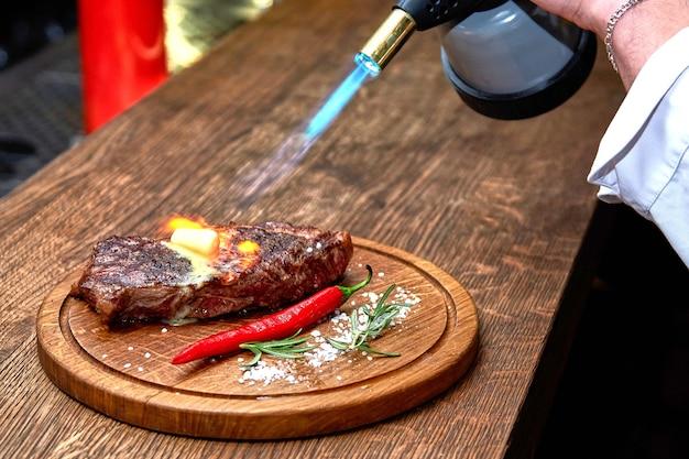 Foco suave. entrecosto de carne carne de bife grelhada com chamas de fogo na tábua de corte de madeira com ramo de alecrim, pimenta e sal. chef master cozinhando um delicioso churrasco. manteiga derretida