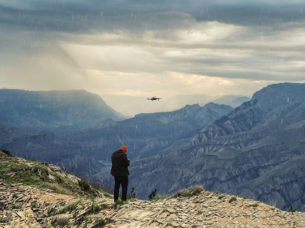 Foco suave. fotógrafo de drones iniciando um dron com mau tempo em um penhasco nas montanhas.