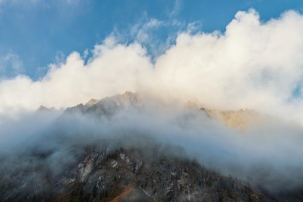 Foco suave. maravilhosa paisagem minimalista com grandes picos de montanhas nevadas acima de nuvens baixas. minimalismo atmosférico com topos de grandes montanhas de neve em céu nublado.