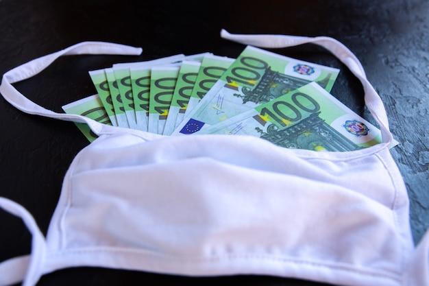 Foco suave ohoto. dinheiro do euro e máscara médica protetora em fundo branco. crise econômica, conceito de desemprego. consequências do isolamento de pessoas com coronavírus durante a quarentena. taxas de inflação.