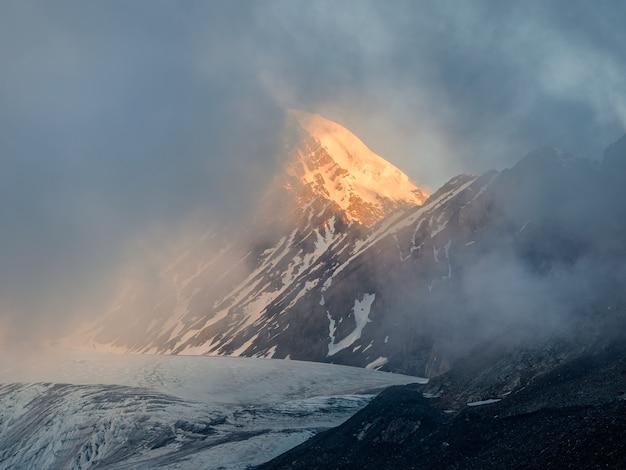 Foco suave. paisagem de montanha minimalista com pico de neve ardente. maravilhosa paisagem minimalista com grandes picos de montanhas nevadas acima de nuvens baixas.