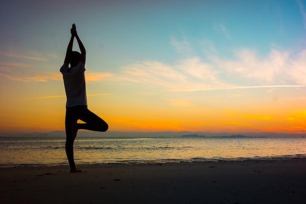 Foco suave silhueta jovem praticando ioga na praia ao pôr do sol