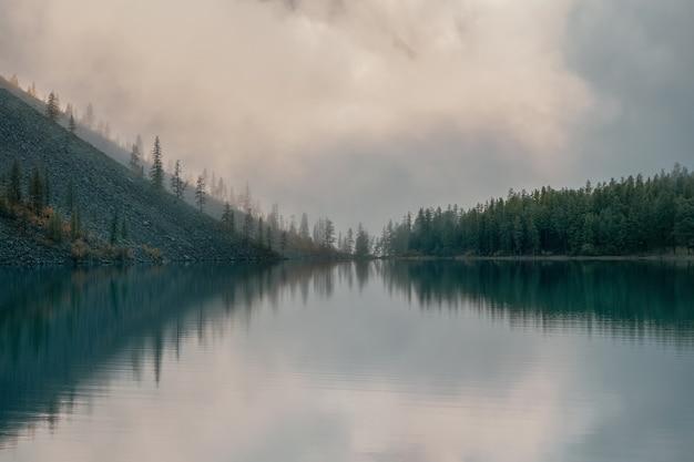 Foco suave. silhuetas da encosta do abeto ao longo do lago da montanha em denso nevoeiro. reflexo de árvores coníferas na água azul. paisagem alpina tranquila no fresco de manhã cedo. cenário atmosférico fantasmagórico.