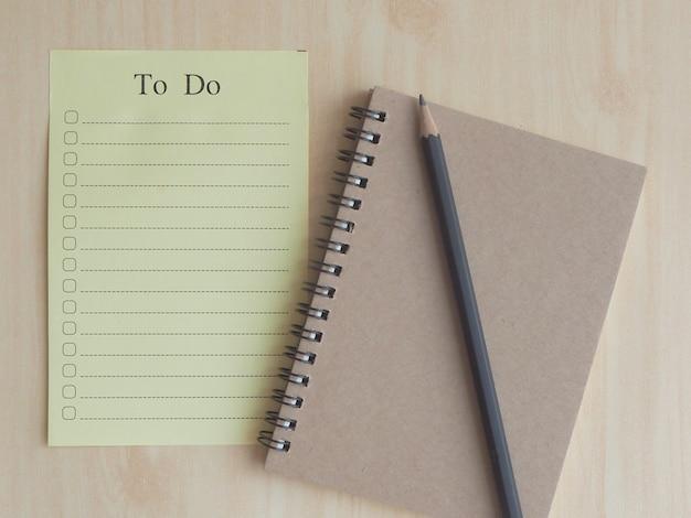 Foco suave to-do list paper com caixa de seleção com lápis preto em um notebook marrom claro