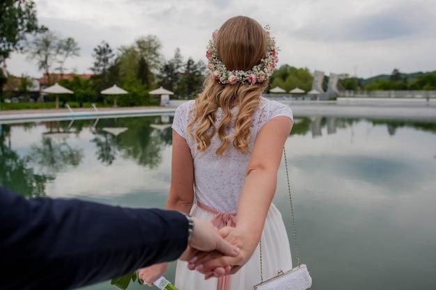 Foco superficial da noiva de mãos dadas com o noivo e caminhando em direção a uma piscina em um resort