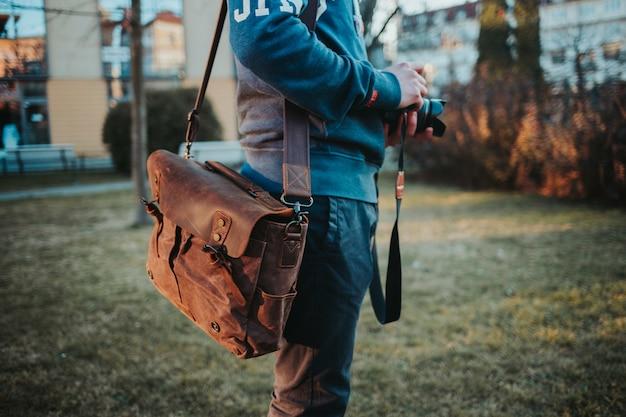 Foco superficial de um homem com uma câmera e uma bolsa de couro marrom