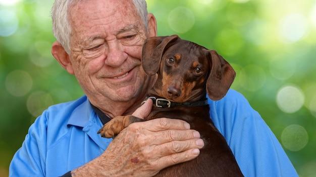 Foco superficial de um homem idoso caucasiano segurando um adorável cachorro dachshund