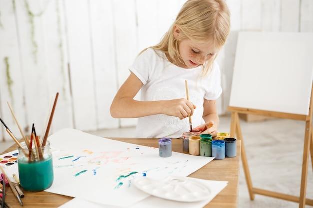 Focou e inspirou a garotinha loira mergulhando o pincel em tinta, misturando-o. criança sardenta feminina em t-shirt branca ocupada com pintura.