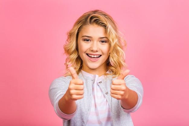 Fofa adorável adorável doce atraente alegre loira pré-adolescente menina abriu a boca mostrando os polegares para cima