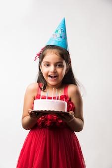 Fofa adorável garotinha indiana ou asiática comemorando aniversário segurando um bolo de morango e soprando velas na mesa ou em pé isolado sobre um fundo branco ou vermelho