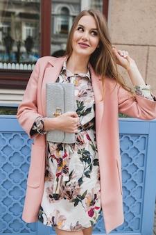 Fofa atraente elegante sorridente mulher andando pelas ruas da cidade com casaco rosa