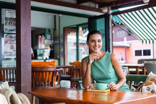 Fofa elegante calma feliz mulher com vestido verde de verão sentada tomando café no café, aproveitando a manhã
