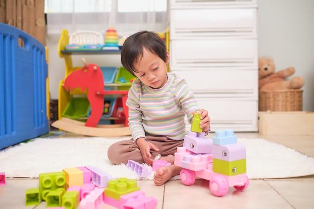 Fofa menina asiática de 2 anos se divertindo brincando com blocos de plástico coloridos no chão em casa