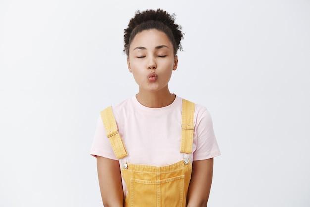 Fofa mulher afro-americana em macacão amarelo, dobrando os lábios para fazer mwah, fechando os olhos e parada apaixonadamente sobre uma parede cinza