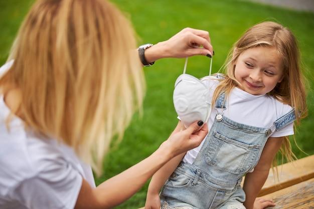 Fofinha criança do sexo feminino se recusando a usar uma máscara protetora no rosto enquanto está sentada ao ar livre