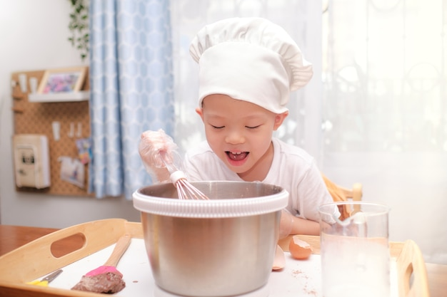 Fofinho feliz sorridente menino asiático de 4 anos se divertindo preparando bolo ou panquecas, aproveite o processo de mistura de massa usando um batedor em casa