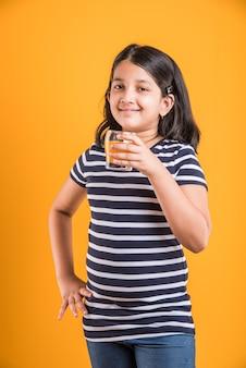 Fofinho menina indiana ou asiática brincalhona bebendo manga fresca ou suco de laranja ou bebida gelada ou bebida em um copo, isolado sobre fundo branco