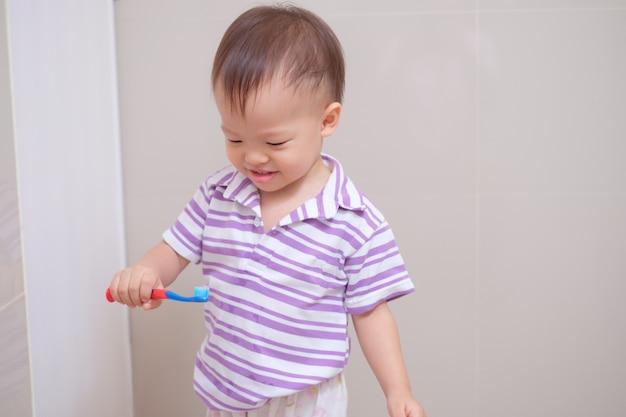 Fofinho sorridente menino asiático criança vestindo uma camisa roxa segurando uma escova de dentes e aprender a escovar os dentes no banheiro em casa