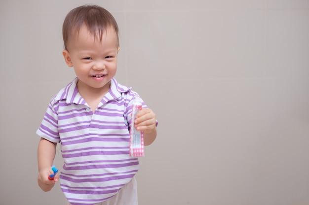 Fofinho sorridente menino asiático criança vestindo uma camisa roxa segurando uma escova de dentes e aprender a escovar os dentes no banheiro em casa Foto Premium
