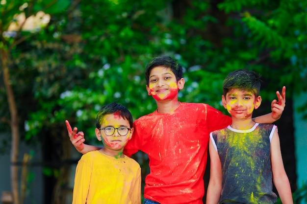 Fofinhos indianos crianças brincando de holi. holi é festival de cores na índia
