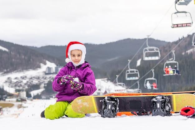 Fofo adorável pré-escolar garoto caucasiano menina retrato menina com chapéu de papai noel e snowboard desfrutar de atividades esportivas de inverno.