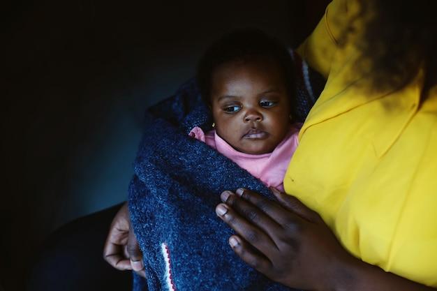 Fofo bebê afro-americano sério nas mãos de mães
