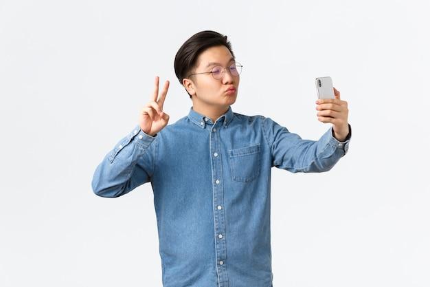 Fofo e engraçado jovem asiático fazendo beicinho bobo, tomando selfie no smartphone, usando o aplicativo de filtro de fotos para mudar a aparência, atirando em si mesmo com o sinal da paz e beijo, fundo branco.