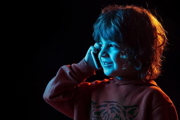 Fofo falando no telefone. fechar-se. retrato do menino caucasiano em fundo escuro do estúdio em luz de néon. lindo modelo cacheado. conceito de emoções humanas, expressão facial, vendas, anúncio, tecnologia moderna, gadgets.