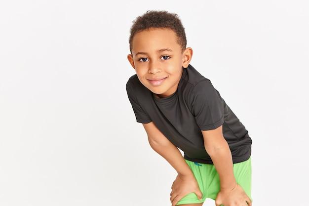 Fofo menino da escola em roupas esportivas, fazendo exercícios na aula de educação física, segurando as coxas