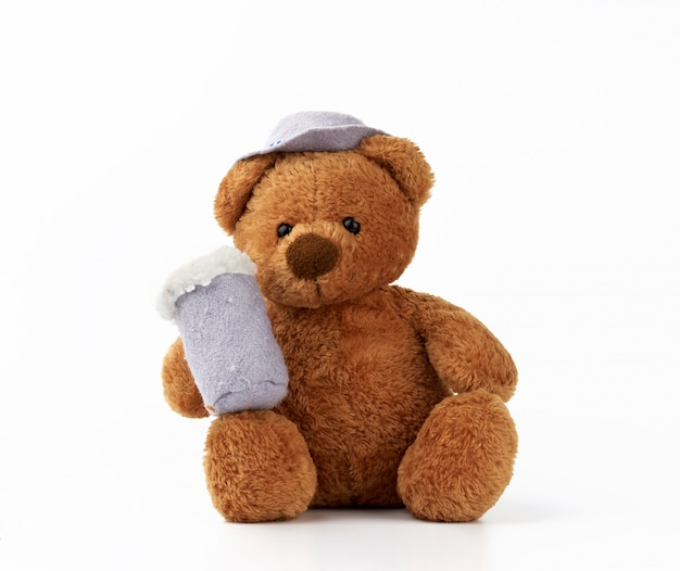 Fofo ursinho marrom detém uma caneca de feltro com espuma e está vestido com um chapéu cinza
