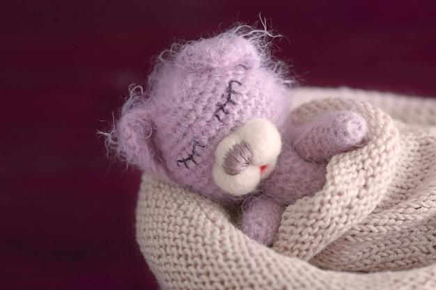 Fofo urso de brinquedo artesanal dormindo em uma bolsa de malha na foto desfocada