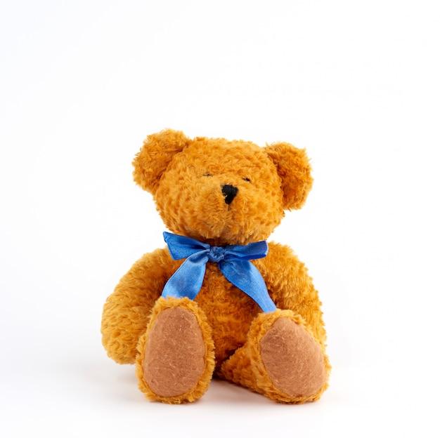 Fofo urso de pelúcia marrom com um laço azul no pescoço