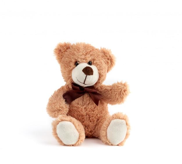 Fofo urso de pelúcia marrom com um laço no pescoço, sente-se sobre um fundo branco